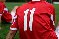 Soccer player wears number 11 sitting on grass (thumbnail)