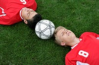 Soccer player lying head to head on grass, football between them (thumbnail)