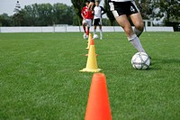 Soccer player running with football slalom around pylons