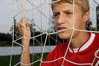 Soccer player clutching at goal net
