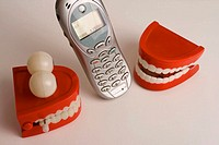 Stock Photo of two sets of Plastic toy teeth talking on a cellphone.One set of teeth has bulging eyes