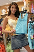 Portrait of a young woman holding a top in a clothing store