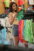 Side profile of a young woman selecting clothes in a clothing store