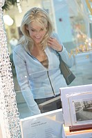Young woman looking in a store window