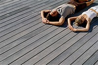 High angle view of a young couple lying on wooden planks (thumbnail)