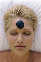 Young woman with a therapeutic stone on her forehead