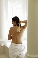 Rear view of a young woman scrubbing her back with a brush