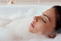Close-up of a young woman taking a bubble bath (thumbnail)