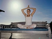 Young woman practicing yoga on a bench