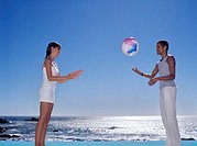 Side profile of a young couple playing with a beach ball