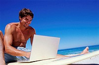 Low angle view of a young man using a laptop on a surfboard