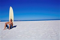 Young man sitting in front of a surfboard on the beach