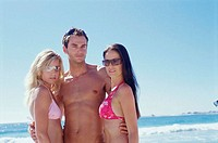 Portrait of a young man standing with two young women on the beach