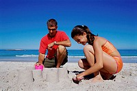 Father and his daughter making a sand castle on the beach