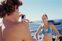 Rear view of a young man taking a photograph of a young woman