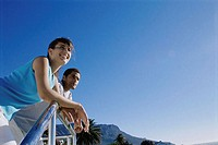 Low angle view of a young couple leaning against a railing