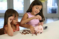 Two sisters counting coins from a piggy bank