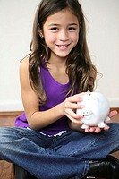 Portrait of a girl holding a piggy bank