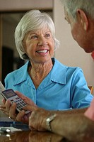 Senior man using a calculator with a senior woman sitting beside him (thumbnail)