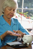 Close-up of a senior woman counting coins