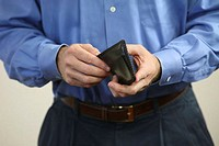 Mid section view of a mid adult man holding a wallet