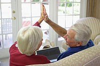 Rear view of a senior couple sitting on a couch and giving a high five to each other