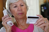 Close-up of a senior woman using a cordless phone holding a credit card