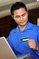 Low angle view of a young man sitting in front of a laptop looking at a credit card