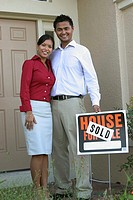 Portrait of a young couple standing outside a house holding a sold sign