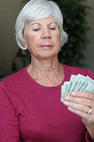 Close-up of a senior woman holding money