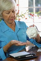 Close-up of a senior woman holding a piggy bank and coins