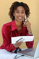 Portrait of a young woman holding a bill using a mobile phone