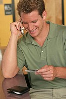 Young man talking on a mobile phone holding a credit card