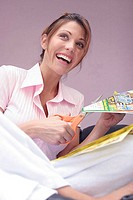 Low angle view of a young woman cutting paper and smiling