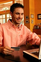 Young man sitting using a laptop holding a credit card