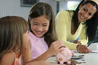 Mother with her two daughters smiling near a piggy bank