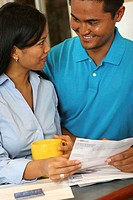 Close-up of a young couple holding a bill