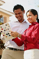 Low angle view of a young couple choosing color from a color swatch