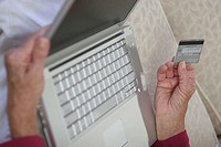 Close-up of a woman's hands holding a credit card and a laptop