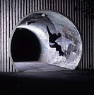 Rear view of a person skateboarding in a tunnel