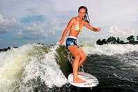 Side profile of a young woman surfing in the sea