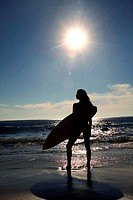 Silhouette of a young woman carrying a surfboard on the beach
