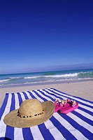 Straw hat and a pair of sandals on a towel at the beach