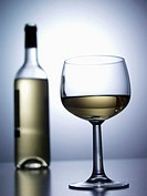 A glass and a bottle of white wine