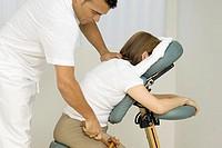 Male physiotherapist helping a woman exercise