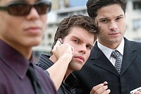 Three young businessmen, one wearing sunglasses and one on mobile phone, close-up, selective focus