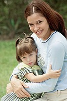 Smiling young woman holding young girl outdoors, close-up