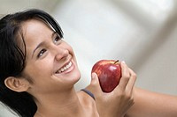 Smiling teenage girl holding apple, close-up, tilt