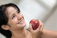 Smiling teenage girl holding apple, close-up, tilt