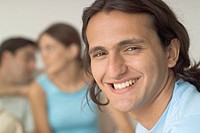 Portrait of smiling man with young couple in background, close-up, selective focus